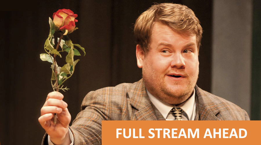 James Cordon on stage holding a rose